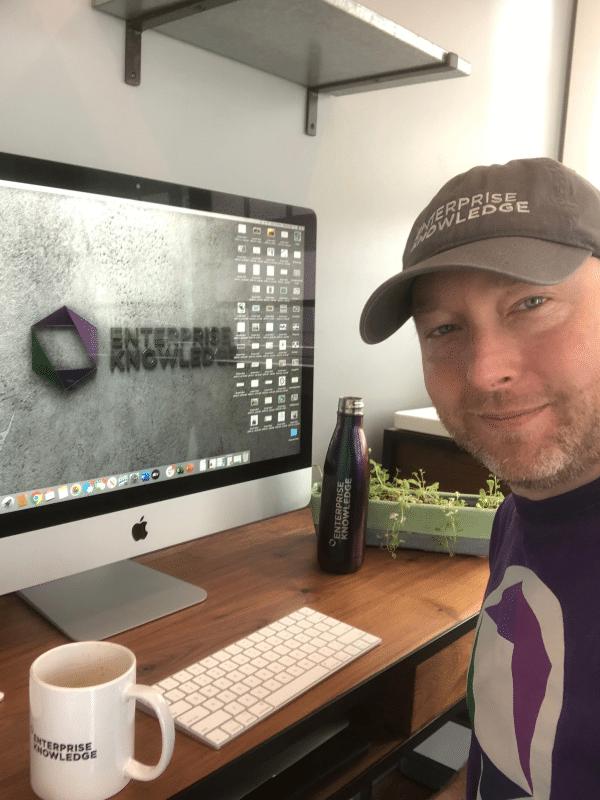EK CEO wearing an EK grey ball cap and EK grey t-shirt sitting at his desktop