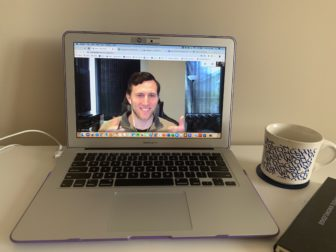 A man on a laptop screen during a video call. The laptop is on a desk with a mug of coffee next to it