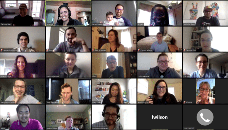 EKers on a video zoom call for a company-wide virtual happy hour. Everyone is smiling.